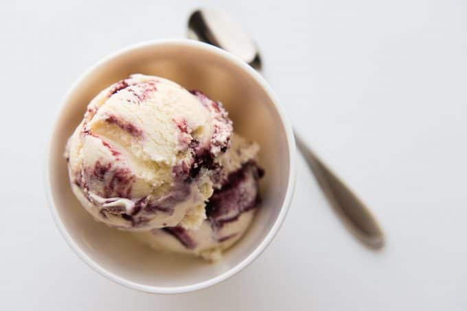 Scoops of vanilla ice cream with blackberry swirls in a small bowl.