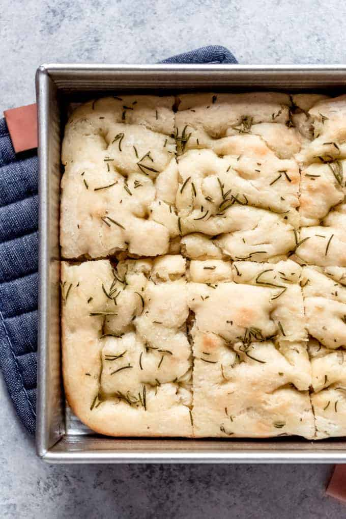An image of a pan of easy focaccia bread cut into rectangles.