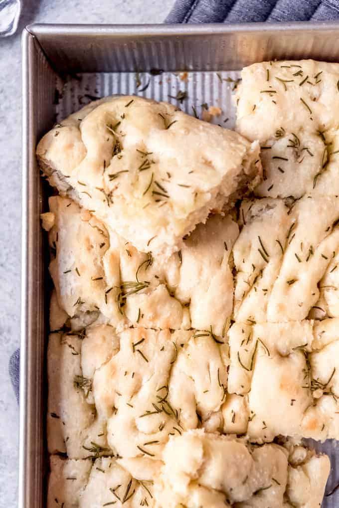 An image of a pan of homemade rosemary focaccia bread cut into rectangles.