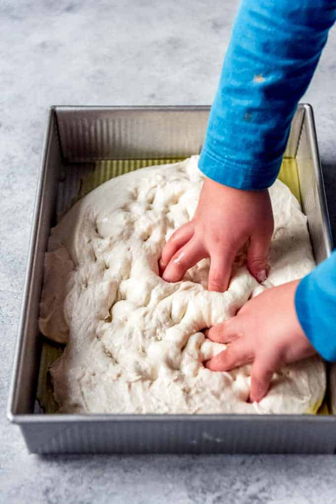 An image of a child's hands poking holes in homemade bread dough.