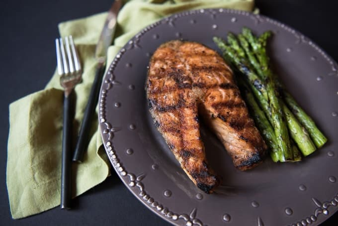 A grilled salmon steak on a plate with grilled asparagus.