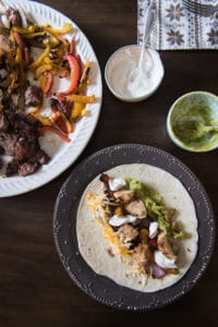 Try these sizzling chicken and steak fajitas made with meat marinated in lime juice, oil, and spices, then grilled alongside peppers and onions and drizzled with reserved marinade!