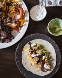 Grilled chicken and steak fajitas with sour cream and guacamole.