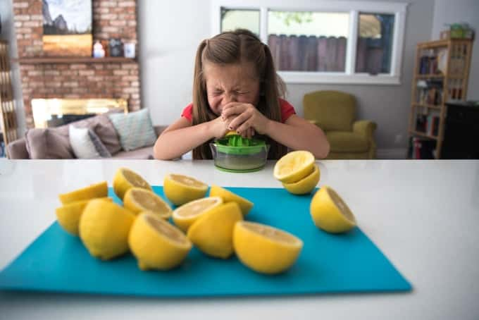 A child squeezing lemons to make lemonade.