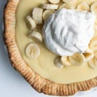 A banana cream pie topped with fresh banana slices and whipped cream.