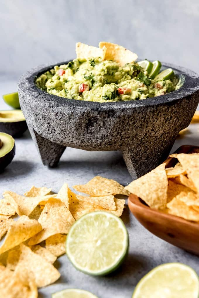 An image of a molcajete stone mortar and pestle filled with homemade guacamole with chips and limes on the side.