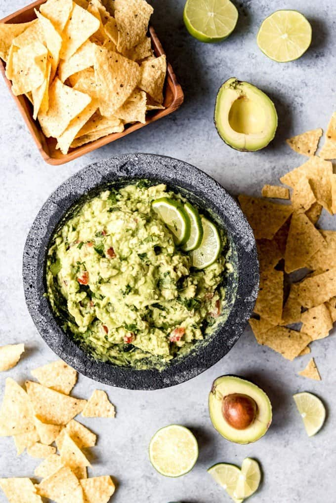 An image of a big bowl of guacamole garnished with sliced limes.