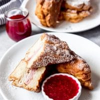 An image of a Monte Cristo ham and cheese sandwich on a white plate with jam for dipping.