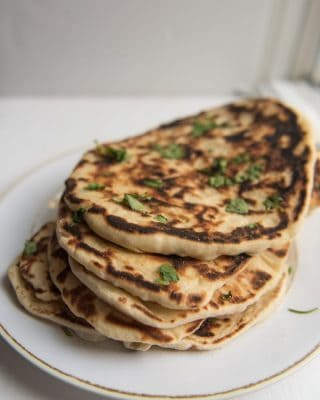 A plate of stacked garlic naan bread.
