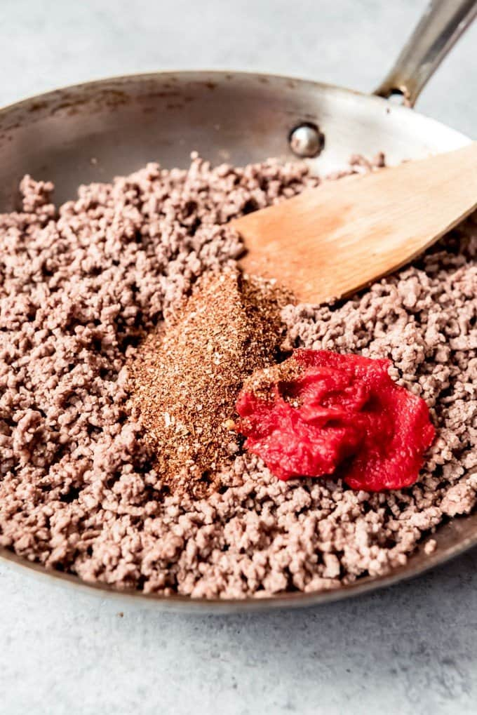 An image of a pan of browned ground beef with homemade taco seasoning and tomato paste.