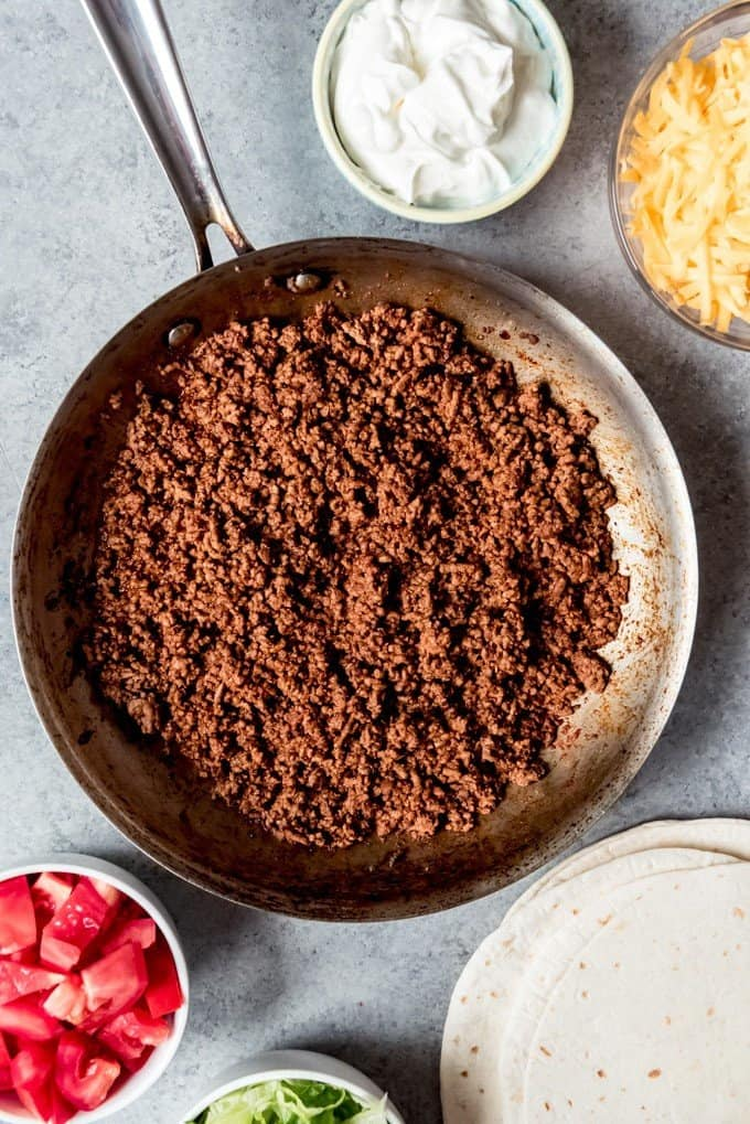 An image of a pan of seasoned ground beef filling for ground beef tacos, surrounded by toppings.