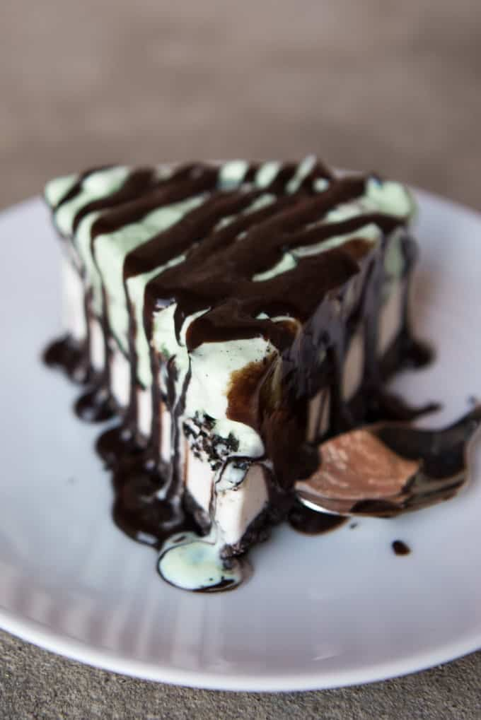 a straight view of a slice of Grasshopper Ice Cream Pie covered in chocolate sauce