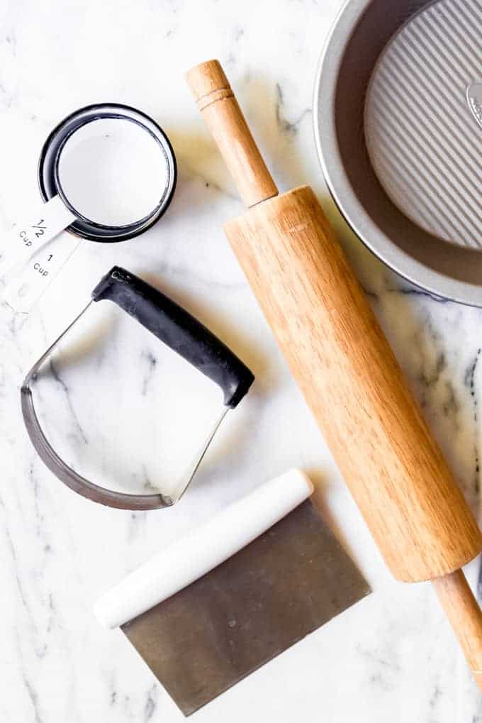 An image of a rollingg pin, measuring cups, pastry cutter, pie plate, and bench scraper.