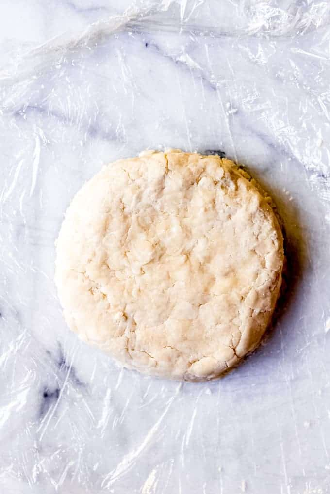 An image of pie crust dough shaped into a disc to be wrapped in plastic wrap and chilled in the fridge.
