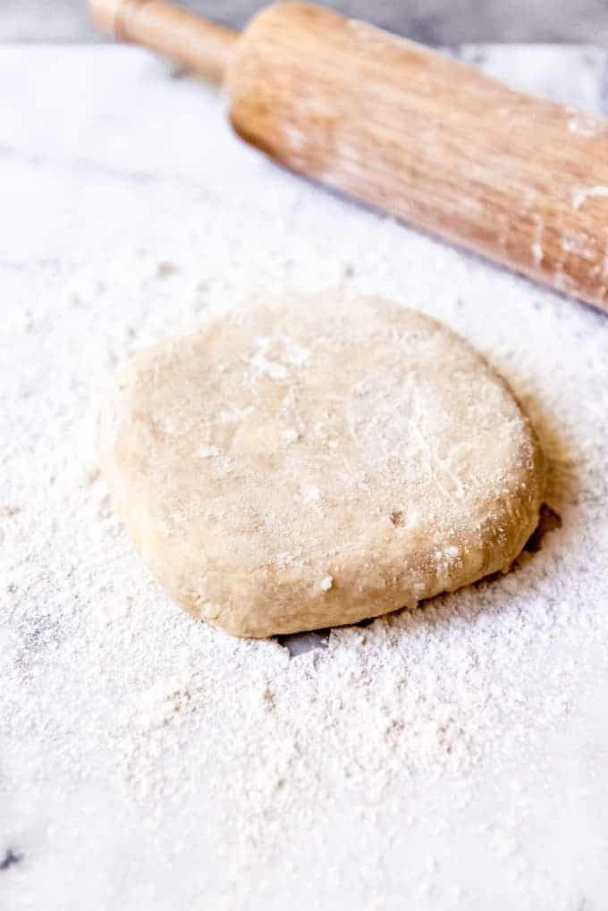 An image of a disc of dough on a floured surface next to a rolling pin.