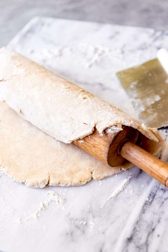An image of an unbaked pie crust rolled onto a rolling pin to transfer to a pie plate.