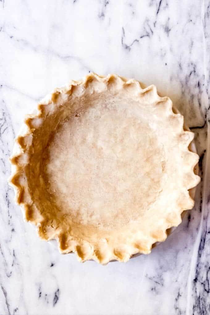 An image of an unbaked pie crust with crimped edges.