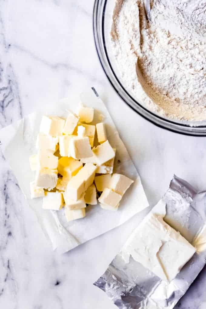 An image of chilled butter cut into cubes next to a bowl of flour and shortening.