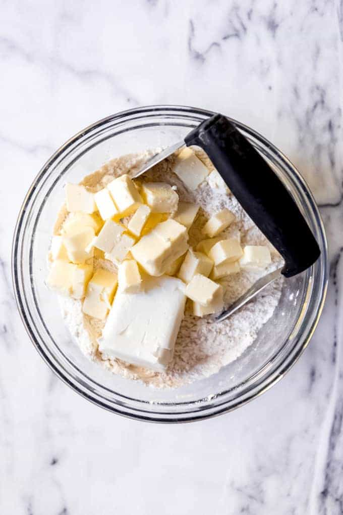 An image of chilled shortening and butter cut into cubes in a bowl of flour and salt to make pie crust.
