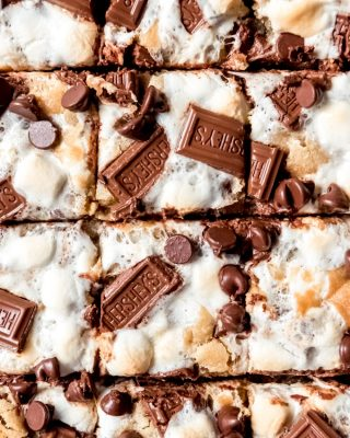 A close-up image of s'mores chocolate chip cookie bars topped with marshmallows and Hershey's chocolate.