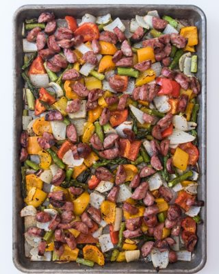 A baking sheet filled with roasted vegetables and sausages.