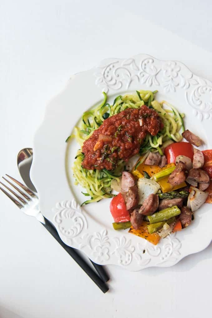 Zucchini noodles with marinara sauce and roasted sausages and vegetables on a white plate.