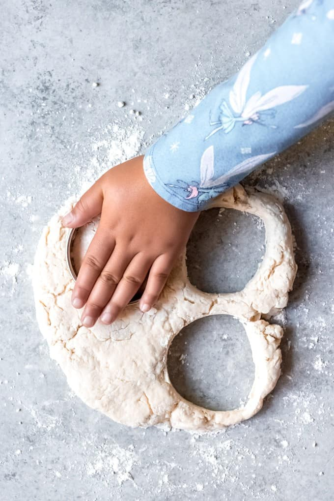 An image of a hand cutting out baking powder biscuit dough.