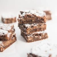 Caramel pecan brownies stacked on top of each other and dusted with powdered sugar.