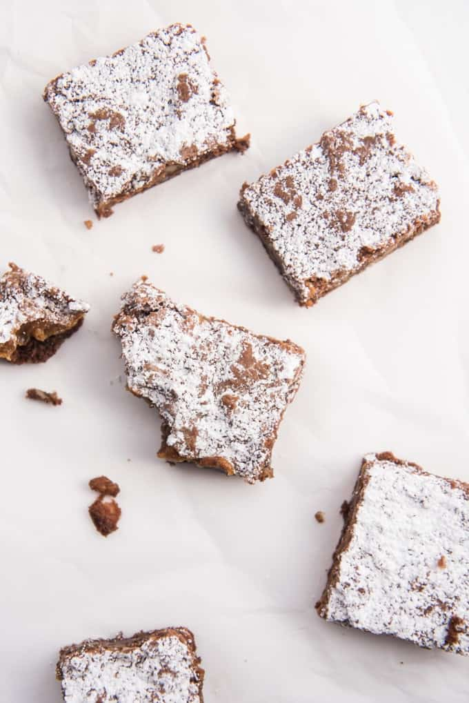 Squares of caramel pecan brownies dusted with powdered sugar on top.