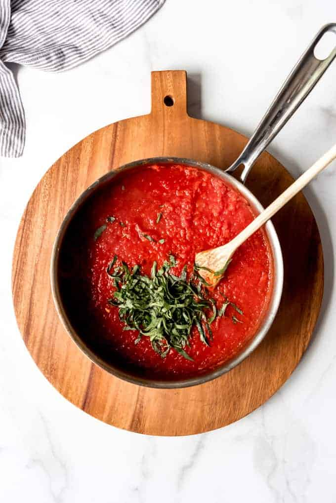 An image of a pan of homemade marinara sauce with fresh basil ribbons sprinkled on top.