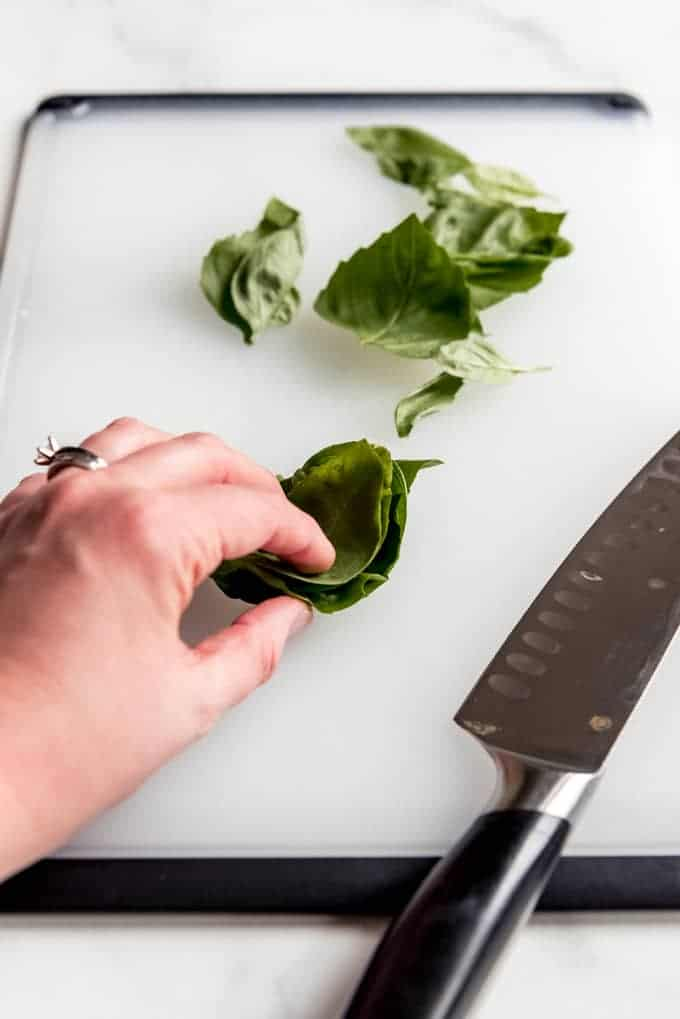 An image of a hand holding a stack of basil leaves to cut them.