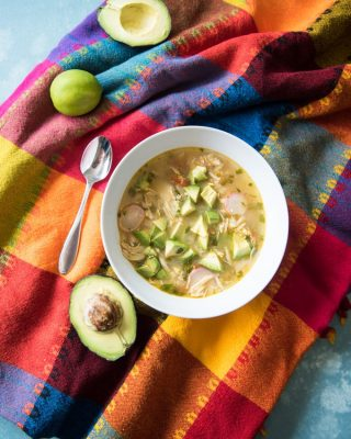 A bowl of chicken avocado lime soup on a brightly colored Mexican tablecloth.