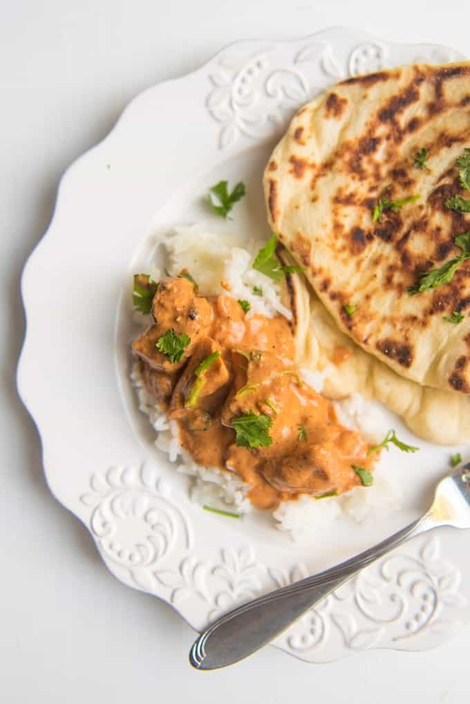 Chicken tikka masala on a white plate with rice and homemade naan.