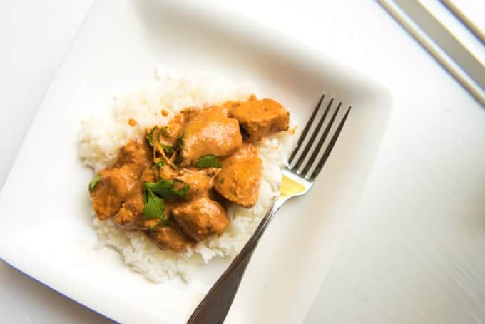 A white plate with chunks of marinated, grilled chicken in a vivid orange tikka sauce over rice.