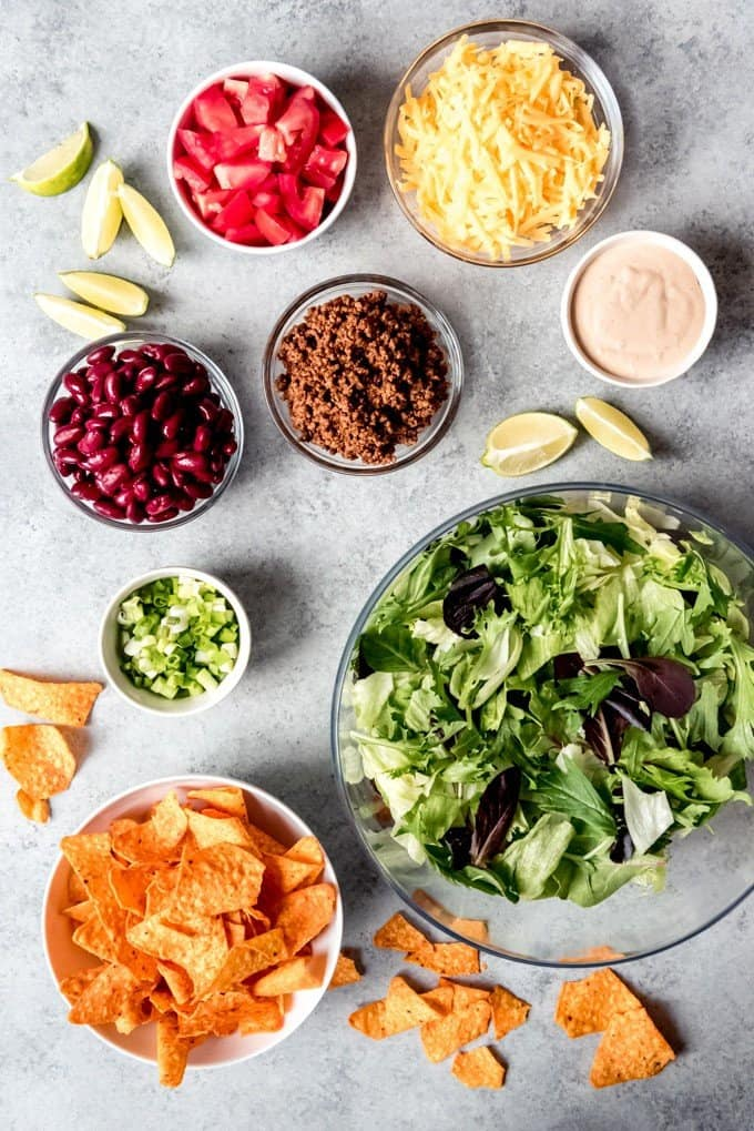An image of taco salad ingredients in separate bowls.