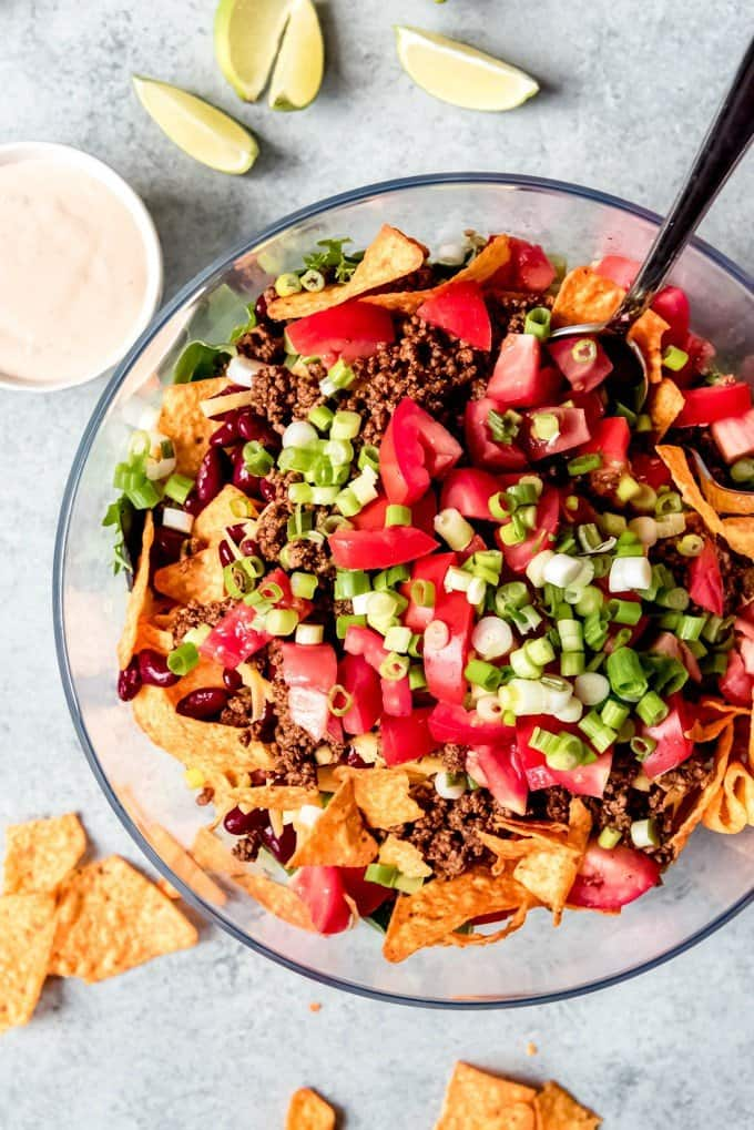 An image of a bowl of taco salad with doritos, taco meat, chopped tomatoes, and green onions.
