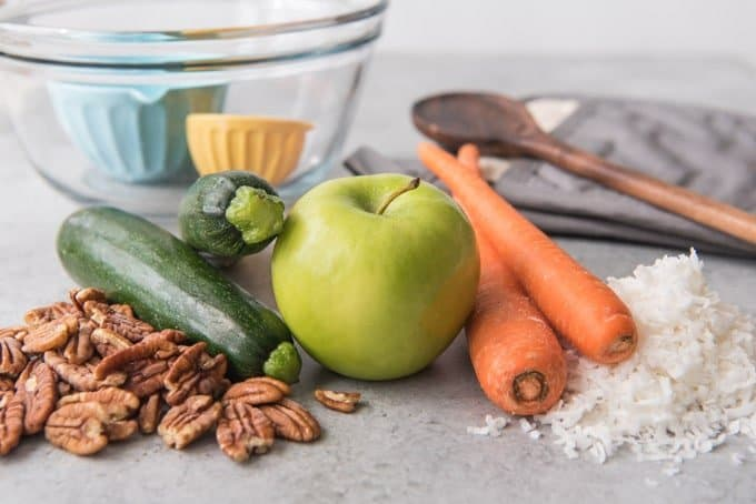 An image of ingredients for morning glory muffins, including pecans, zucchini, apple, carrots, and coconut.