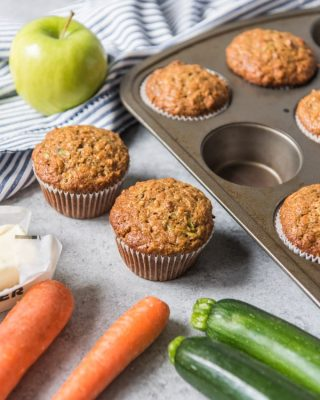 Morning glory muffins with carrots, zucchini and apple next to them.