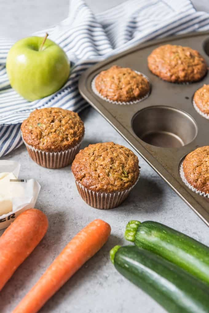 Morning glory muffins next to carrots, zucchini, and an apple.
