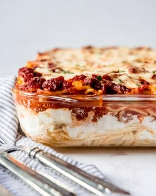 An image of a baked spaghetti casserole in a glass baking dish.