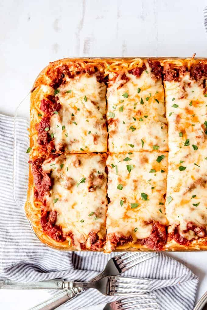 An image of a sliced baked pasta casserole with melted mozzarella cheese on top.