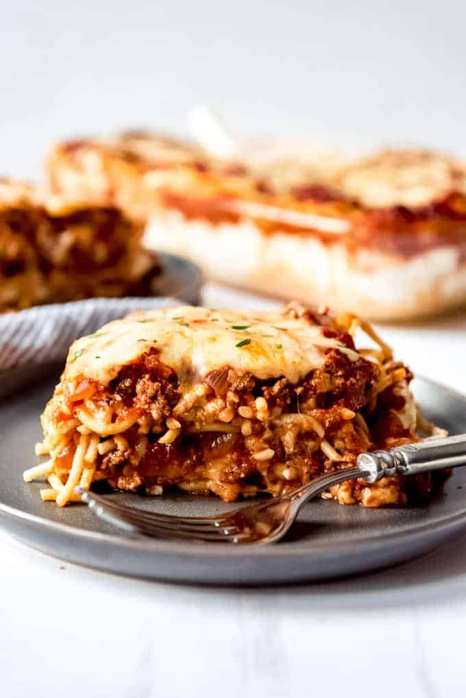 An image of a serving of baked spaghetti casserole on a plate with a fork.