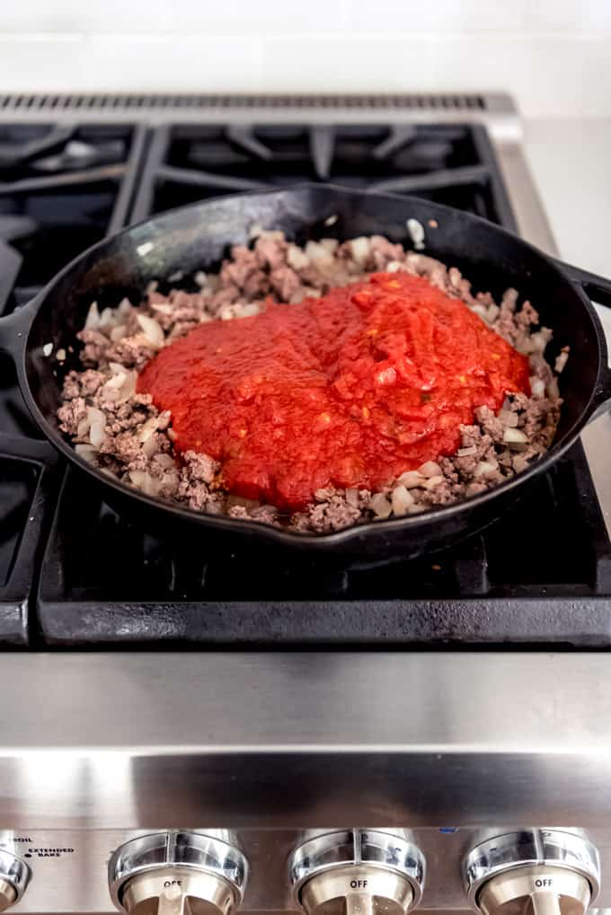 An image of browned ground beef and onions in a large cast iron skillet with spaghetti sauce poured on top.