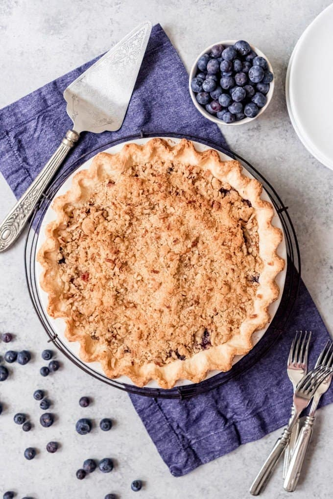 An image of a whole blueberry pie with pecan streusel topping.