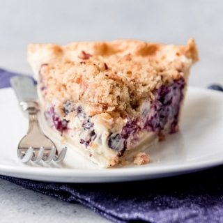 "Juicy fresh blueberries, creamy sour cream custard, buttery streusel crumble topping with chopped pecans, all in a flaky crust - this Blueberry Sour Cream Custard Pie won the ""Pie Most Likely To Bring About World Peace"" award at our annual Pi Day pie party in 2016 for good reason."