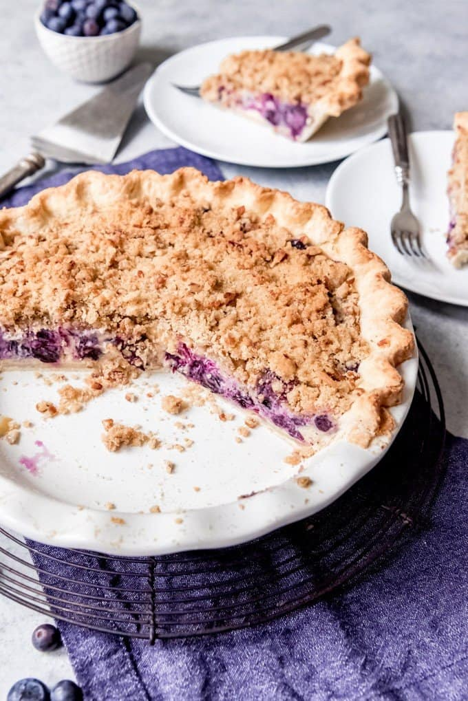 An image of a blueberry custard pie with slices already taken out of it and placed on plates nearby.