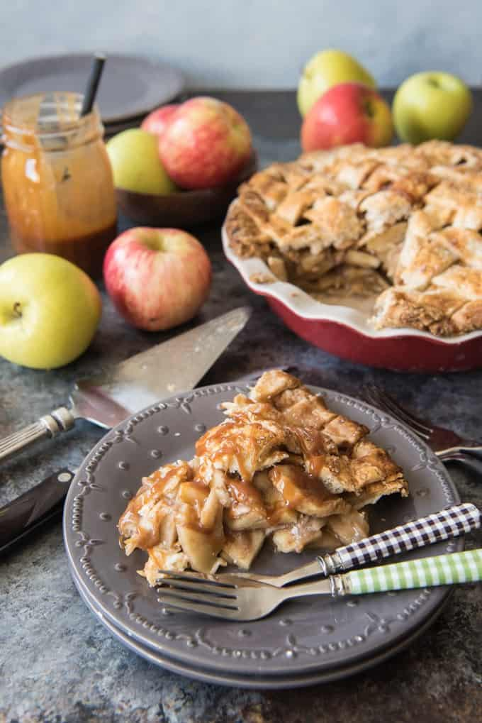 a slice of salted caramel apple pie on a stack of gray plates with forks in front of more apples and pie
