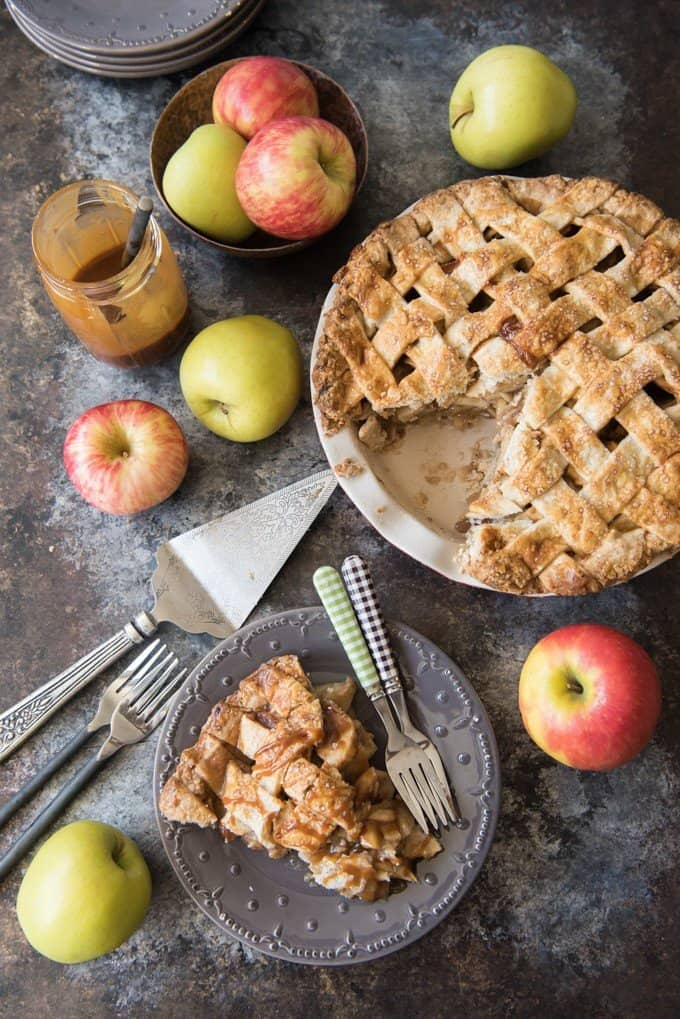 an aerial view of salted caramel apple pie, a plate with a slice and apples