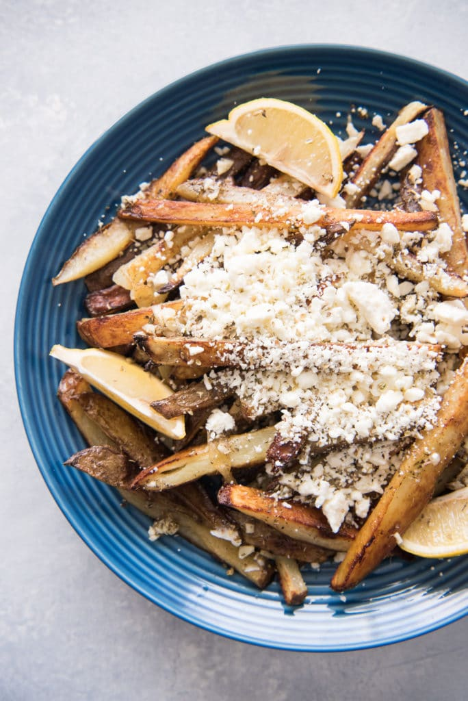 a blue plate topped with fries and feta cheese with sliced lemon as garnish