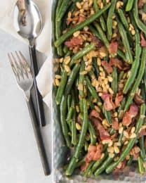 green beans with pine nuts and bacon on a pan next to utensils